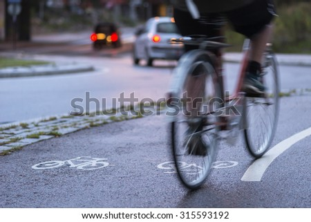 Cyclist in blurred motion on cycling path by busy street at night
