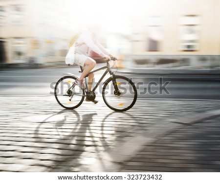 cyclist in blurred motion on modern bike on street in bright sunshine - stock photo