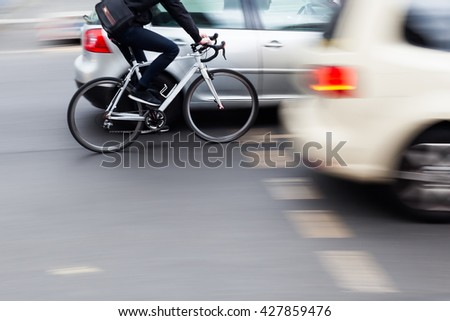 cyclist in city traffic in motion blur - stock photo