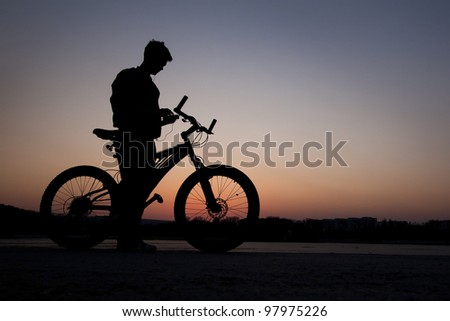 cyclist listen music on city background at the sunset - stock photo