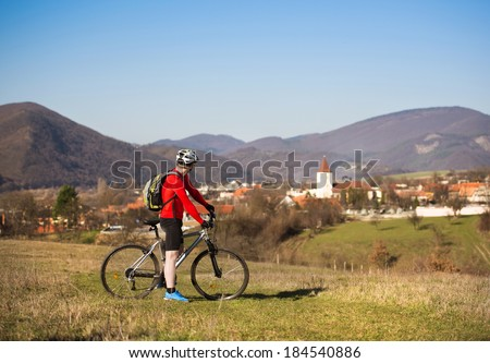 cyclist man is taking break and observing the view - stock photo