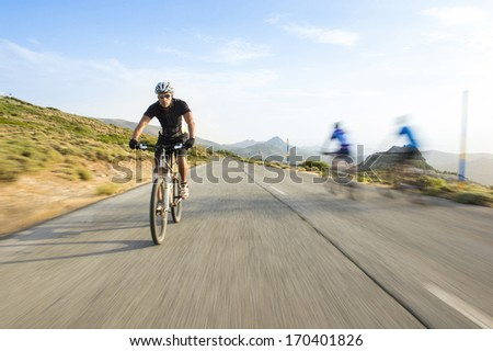 Cyclist man riding mountain bike in sunny day on a mountain road - stock photo