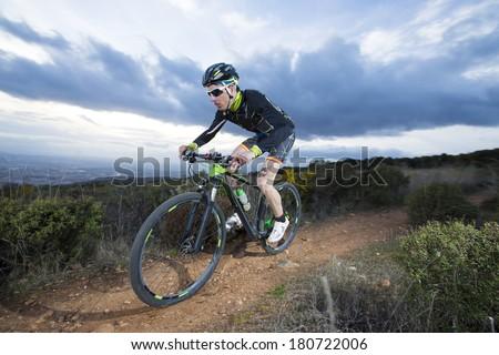 Cyclist man riding mountain bike on mountain. - stock photo
