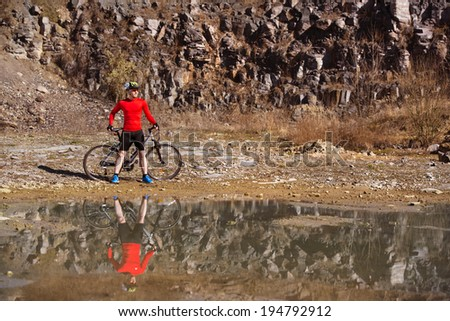 Cyclist man standing with his bike is reflecting in water puddle - stock photo