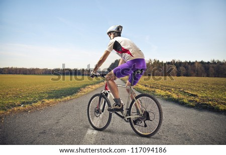 Cyclist on a long road of countryside - stock photo