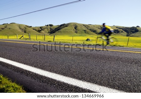 Cyclist on a rural road - stock photo