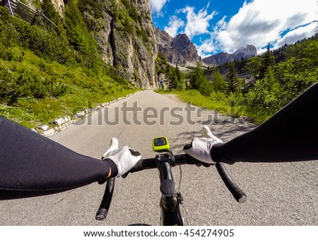 Cyclist on mountainous road in a sunny day. Cycling in Dolomites, Passo Falzarego. POV Original point of view