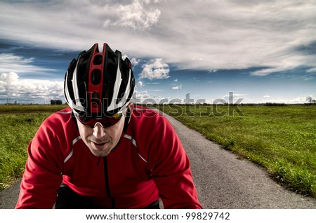 Cyclist on road bike through a asphalt road and blue sky with clouds. - stock photo