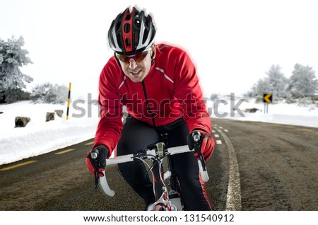 Cyclist on road bike through a asphalt road in the mountains with snow. - stock photo