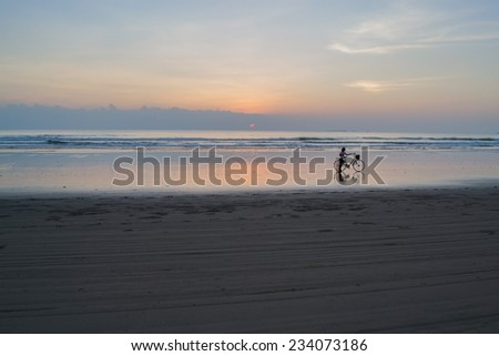 Cyclist on the beach in the sunset. - stock photo