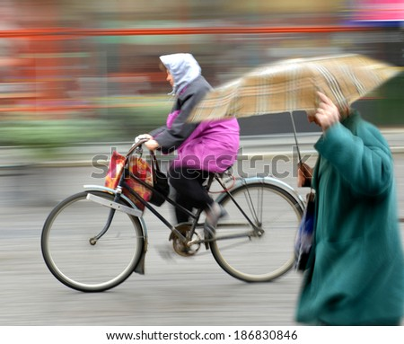 Cyclist on the city roadway in rainy day in motion blur - stock photo