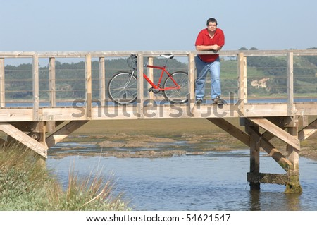 cyclist on the seaside over wooden bridge looking to the landscape resting - stock photo