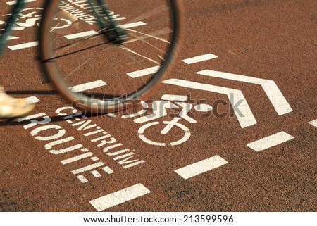 Cyclist passing by over a bicycle sign for the city center on an urban cycle path. - stock photo