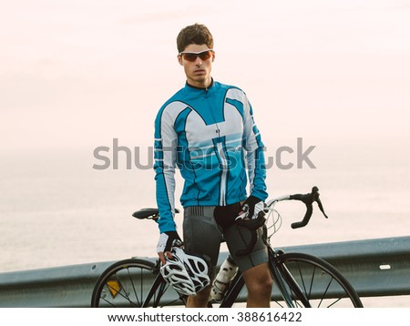 Cyclist portrait outdoors, he is looking at camera. - stock photo