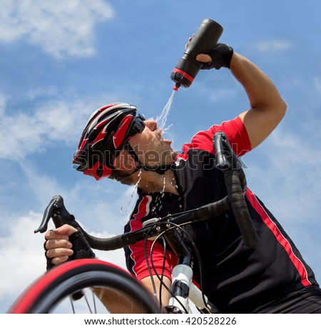 cyclist refreshes from a bottle while riding bicycle. Cyclist on the background of blue  pouring water on his head. Tired cyclist refreshes splashing water - stock photo