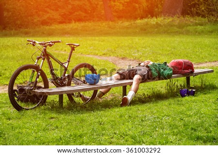 Cyclist resting on a bench in the park. Tired young man with his mountain bike in the forest resting and making pause. Adventure, travel, tourism and sports activity concept