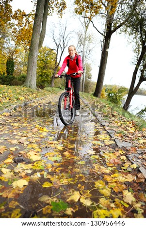 Cyclist ride through a puddle after rain in the autumn park