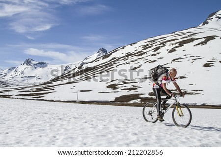Cyclist rides in Leirdalen over a snow-covered road - stock photo