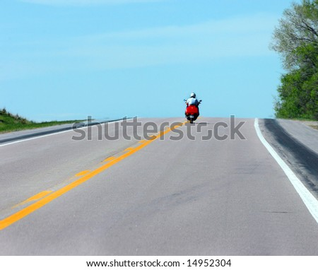 Cyclist rides into the wild blue yonder as his motorcycle tops a hill.  Red cycle. - stock photo