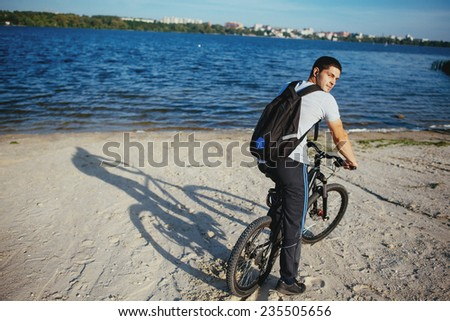 Cyclist riding a bicycle in Macedonia with a sun in the background  - stock photo
