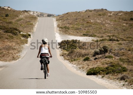 Cyclist riding bike down desert road - stock photo