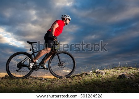 Cyclist riding mountain bike on trail at evening against cloudy sky
