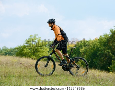 Cyclist Riding the Bike on the Trail in the Beautiful Autumn Forest - stock photo