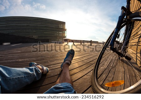 cyclist sitting and resting with the wheel of mountain bike at the sunset, POV view - stock photo
