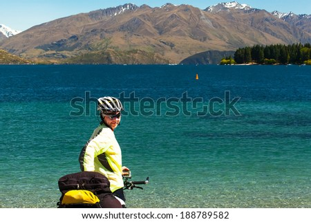 cyclist stands on the winding gravel mountain road near Lake Wanaka  New Zealand,  on a background of blue sky with clouds, snowy Southern Alps.