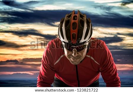 Cyclist with helmet against cloudy sunset sky. - stock photo