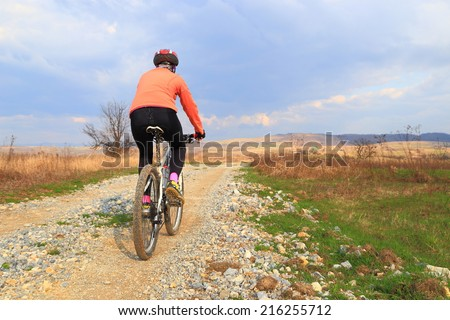 Cyclist woman rides a bike on a dirt road in the open field