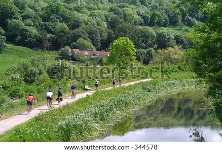 Cyclists alongside a canal - stock photo