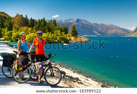 cyclists are on the winding gravel mountain road near Lake Pukaki view from Glentanner Park Centre near Mount Cook, on a background of blue sky with clouds, snowy Southern Alps. - stock photo