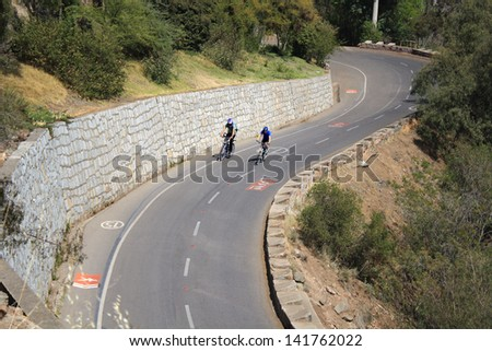Cyclists in the street of a hill - stock photo
