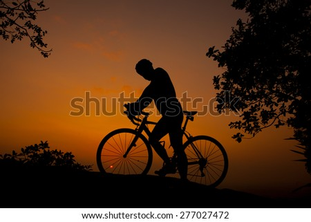 Cyclists, mountain, sky orange.
