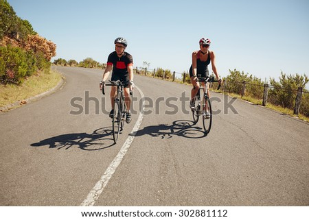 Cyclists riding down a scenic country road. Triathletes racing on a bicycle on a country road - stock photo