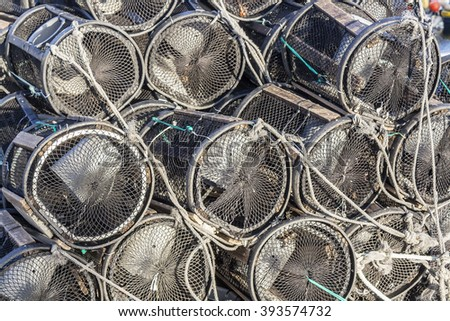 Cylindrical pound nets piled on the dock - stock photo