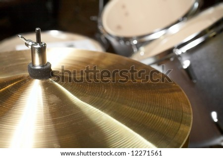 Cymbal closeup with drum set in background - stock photo
