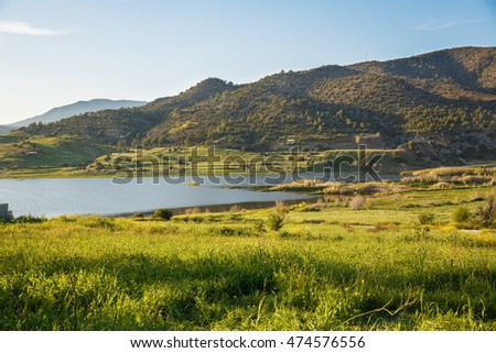 Cyprus landscape with mountains, lake and village.