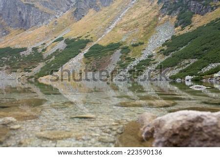 Czarny Staw alpine lake in autumn colours, High Tatra Mountains, Poland - stock photo