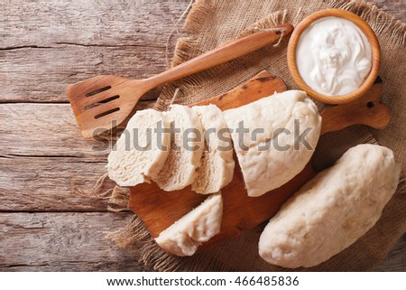 Czech cuisine: sliced boiled knedliks close-up on chopping board and sour cream. horizontal view from above