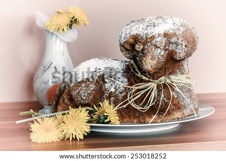 Czech Easter - baked lamb with powdered sugar and vase with dandelions on wood desk - stock photo