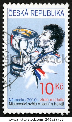 CZECH REPUBLIC - CIRCA 2010: post stamp printed in Ceska (Czechoslovakia) shows player kissing gold medal trophy in ice hockey world championships IIHF; Germany; Scott 3461 10k blue, circa 2010 - stock photo