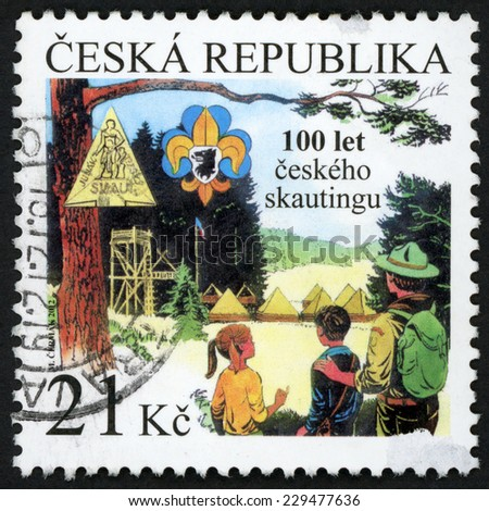 CZECH REPUBLIC - CIRCA 2012: post stamp printed in Czechoslovakia (Ceska) shows scout (junak) with two kids in camp; 100th anniversary foundation of Czech scout movement; 21k multicolor, circa 2012 - stock photo