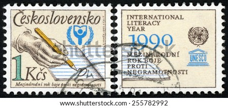 CZECHOSLOVAKIA - CIRCA 1990: stamp printed in Czech (Ceskoslovensko) shows hand with pencil writing letter A in lined notebook & UNESCO emblems; UNESCO world literacy year; Scott 2770 1k; circa 1990 - stock photo