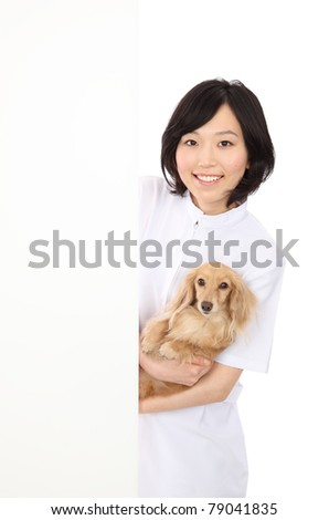 Dachshund with an empty board with Asian women - stock photo