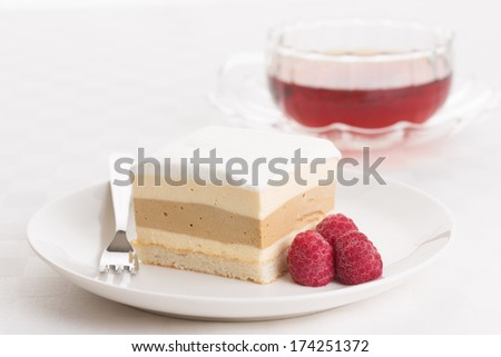 Dacquoise cake of Bavarian cream, coffee-flavored hazelnut praline, and almond meringue, topped with whipped cream. Garnished with raspberry and served with a cup of tea. - stock photo
