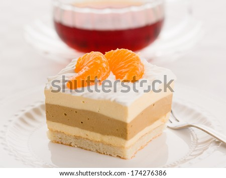Dacquoise cake of Bavarian cream, coffee-flavored hazelnut praline, and almond meringue, topped with whipped cream. Garnished with pieces of mandarin orange and served with a cup of tea. - stock photo