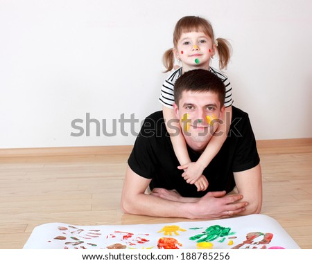 Dad and daughter drawing with colored finger paint - stock photo