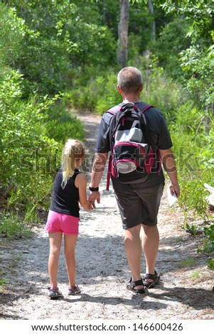dad and daughter exploring a nature path - stock photo